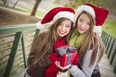 Δύο χαμόγελο των καπέλων Santa γυναικών που κρατούν ένα τυλιγμένο δώρο στοκ φωτογραφία με δικαίωμα ελεύθερης χρήσης