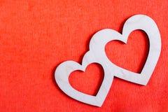 Δύο χαρασμένες ξύλινες καρδιές βρίσκονται διαγώνια στο κόκκινο κατασκευασμένο PA Στοκ φωτογραφίες με δικαίωμα ελεύθερης χρήσης