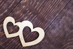 Δύο χαρασμένες ξύλινες καρδιές βρίσκονται διαγώνια χρωματισμένες στις σκοτάδι διαγώνιες κατασκευασμένες σανίδες με το διάστημα αν Στοκ φωτογραφία με δικαίωμα ελεύθερης χρήσης