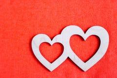 Δύο χαρασμένες ξύλινες καρδιές βρίσκονται στο κόκκινο κατασκευασμένο backgro εγγράφου Στοκ φωτογραφία με δικαίωμα ελεύθερης χρήσης