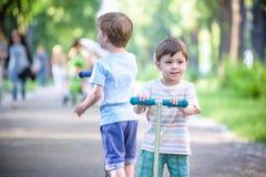 Δύο χαριτωμένα αγόρια, ανταγωνίζονται στην οδήγηση των μηχανικών δίκυκλων, υπαίθριων στο πάρκο, καλοκαίρι Στοκ φωτογραφίες με δικαίωμα ελεύθερης χρήσης