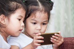 Δύο χαριτωμένα ασιατικά κορίτσια παιδιών που έχουν τη διασκέδαση για να παίξει το παιχνίδι στο smartphone Στοκ Φωτογραφία