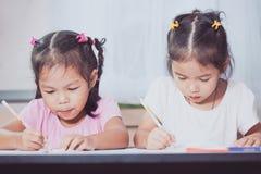 Δύο χαριτωμένα ασιατικά κορίτσια παιδιών που έχουν τη διασκέδαση που σύρει και που χρωματίζει από κοινού Στοκ Εικόνες