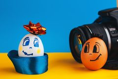 Δύο χαριτωμένα, κομψά αυγά με τα πρόσωπα, που θέτουν μπροστά από τη κάμερα Πάσχα ένας χρόνος να ντυθεί επάνω ο πίνακάς σας στοκ φωτογραφία με δικαίωμα ελεύθερης χρήσης
