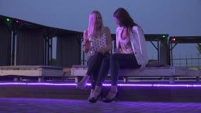 Δύο χαριτωμένα κορίτσια που πίνουν τα κοκτέιλ σε ένα νυχτερινό κέντρο διασκέδασης Οι φίλες κάθονται με τα κοκτέιλ και κουβεντιάζο απόθεμα βίντεο
