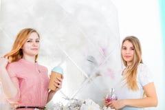 Δύο χαριτωμένα κορίτσια στα φορέματα πίνουν τα ποτά από τα φλυτζάνια με τα καπάκια και το τ Στοκ Εικόνες