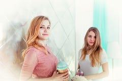 Δύο χαριτωμένα κορίτσια στα φορέματα πίνουν τα ποτά από τα φλυτζάνια με τα καπάκια και το τ Στοκ εικόνα με δικαίωμα ελεύθερης χρήσης
