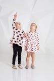 Δύο χαριτωμένα μικρά κορίτσια που στέκονται στα ρόδινα ενδύματα με τις μαύρες καρδιές στο άσπρο υπόβαθρο τοίχων στο στούντιο Στοκ εικόνα με δικαίωμα ελεύθερης χρήσης
