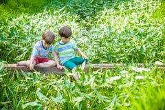 Δύο χαριτωμένα μικρά παιδιά που κάθονται σε μια ξύλινη γέφυρα Στοκ Εικόνες