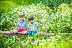 Δύο χαριτωμένα μικρά παιδιά που κάθονται σε μια ξύλινη γέφυρα Στοκ Εικόνα
