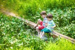 Δύο χαριτωμένα μικρά παιδιά που κάθονται σε μια ξύλινη γέφυρα Στοκ εικόνες με δικαίωμα ελεύθερης χρήσης