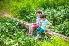 Δύο χαριτωμένα μικρά παιδιά που κάθονται σε μια ξύλινη γέφυρα Στοκ φωτογραφία με δικαίωμα ελεύθερης χρήσης