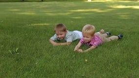 Δύο χαριτωμένα μικρά παιδιά στα πουκάμισα που βρίσκονται στην πράσινη χλόη και που χαμογελούν, πορτρέτο φιλμ μικρού μήκους