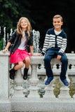 Δύο χαριτωμένα παιδιά κάθονται στο κιγκλίδωμα Μαρμάρινος-πέτρινη πηγή στοκ φωτογραφία