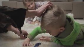 Δύο χαριτωμένα παιδιά που βάζουν στο πάτωμα στο χνουδωτό τάπητα που παίζει τα παιχνίδια τους στο σπίτι Αρσενικό χέρι που κτυπά έν φιλμ μικρού μήκους
