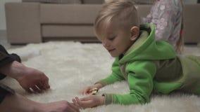 Δύο χαριτωμένα παιδιά που βάζουν στο χνουδωτό τάπητα στο παιχνίδι πατωμάτων με τα παιχνίδια στο σπίτι Αρσενικό χέρι σχετικά με τη φιλμ μικρού μήκους