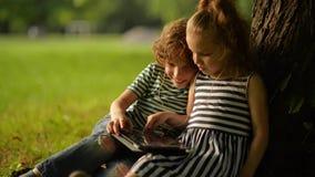 Δύο χαριτωμένα παιδιά που χρησιμοποιούν την ψηφιακή ταμπλέτα στο θερινό κήπο φιλμ μικρού μήκους