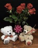 Δύο χαριτωμένες για χάδια teddy αρκούδες με τα κόκκινα τριαντάφυλλα στο βάζο και το ρόδινο τόξο στον ξύλινο πίνακα στο σκοτεινό υ στοκ φωτογραφία