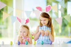 Δύο χαριτωμένες μικρές αδελφές που φορούν τα αυτιά λαγουδάκι που παίζουν το κυνήγι αυγών σε Πάσχα στοκ εικόνα με δικαίωμα ελεύθερης χρήσης