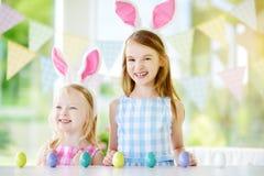Δύο χαριτωμένες μικρές αδελφές που φορούν τα αυτιά λαγουδάκι που παίζουν το κυνήγι αυγών σε Πάσχα Στοκ φωτογραφία με δικαίωμα ελεύθερης χρήσης