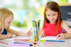Δύο χαριτωμένες μικρές αδελφές που σύρουν με τα ζωηρόχρωμα μολύβια σε μια φύλαξη Δημιουργικά παιδιά που χρωματίζουν από κοινού Στοκ Εικόνες