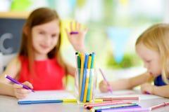 Δύο χαριτωμένες μικρές αδελφές που σύρουν με τα ζωηρόχρωμα μολύβια σε μια φύλαξη Δημιουργικά παιδιά που χρωματίζουν από κοινού Στοκ φωτογραφίες με δικαίωμα ελεύθερης χρήσης