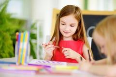 Δύο χαριτωμένες μικρές αδελφές που σύρουν με τα ζωηρόχρωμα μολύβια σε μια φύλαξη Δημιουργικά παιδιά που χρωματίζουν από κοινού Στοκ φωτογραφία με δικαίωμα ελεύθερης χρήσης