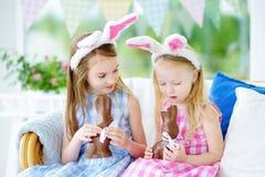 Δύο χαριτωμένες μικρές αδελφές που φορούν τα αυτιά λαγουδάκι που τρώνε τα κουνέλια Πάσχας σοκολάτας Στοκ Εικόνα