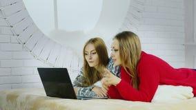 Δύο χαριτωμένες φίλες στα εγχώρια ενδύματά τους βρίσκονται στο κρεβάτι και κουβεντιάζουν στο skype με τους φίλους απόθεμα βίντεο