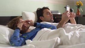 Δύο χαριτωμένοι αδελφοί στις πυτζάμες που βρίσκονται στο κρεβάτι στην κρεβατοκάμαρα το πρωί Ο παλαιότερος αδελφός στο τηλέφωνο κυ απόθεμα βίντεο