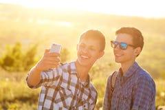 Δύο χαριτωμένοι τύποι παίρνουν selfies τους ευτυχείς φίλους φωτογραφίζονται στο τηλέφωνο στοκ φωτογραφία