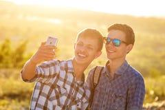Δύο χαριτωμένοι τύποι παίρνουν selfies τους ευτυχείς φίλους φωτογραφίζονται στο τηλέφωνο στοκ φωτογραφίες