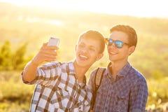 Δύο χαριτωμένοι τύποι παίρνουν selfies τους ευτυχείς φίλους φωτογραφίζονται στο τηλέφωνο στοκ φωτογραφία με δικαίωμα ελεύθερης χρήσης
