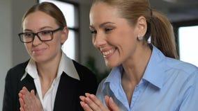Δύο χαρούμενοι υπάλληλοι που χτυπούν τα χέρια, που διαβάζουν τις καλές ειδήσεις, επιχειρησιακό επίτευγμα απόθεμα βίντεο