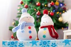 Δύο χειροποίητοι χιονάνθρωποι με το υπόβαθρο Χριστουγέννων στην άσπρη γούνα Στοκ Εικόνες