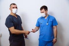 Δύο χειρούργοι στις αποστειρωμένες στολές με τα ιατρικά όργανα στο άσπρο υπόβαθρο στο νοσοκομείο Στοκ φωτογραφίες με δικαίωμα ελεύθερης χρήσης
