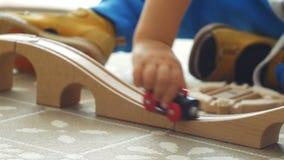Δύο χρονών παιχνίδια αγοριών με τον ξύλινο σιδηρόδρομο σε ένα ηλιόλουστο δωμάτιο απόθεμα βίντεο