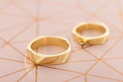 Δύο χρυσά γαμήλια δαχτυλίδια στο ρόδινο υπόβαθρο κρητιδογραφιών Στοκ Φωτογραφίες