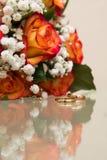 Δύο χρυσά γαμήλια δαχτυλίδια βρίσκονται σε μια ανθοδέσμη Στοκ Φωτογραφία