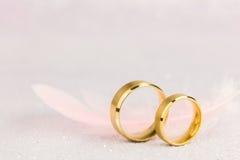 Δύο χρυσά γαμήλια δαχτυλίδια και ελαφρύ φτερό αγγέλου Στοκ Εικόνες