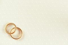 Δύο χρυσά γαμήλια δαχτυλίδια πέρα από την άσπρη γαμήλια δαντέλλα με το floral σχέδιο Στοκ Εικόνες