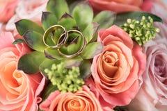 Δύο χρυσά γαμήλια δαχτυλίδια στην ανθοδέσμη στα τριαντάφυλλα και succulent στοκ φωτογραφία με δικαίωμα ελεύθερης χρήσης
