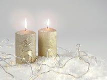 Δύο χρυσά candlelights με μια λαμπρή ελαφριά αλυσίδα στο χιόνι Στοκ εικόνα με δικαίωμα ελεύθερης χρήσης