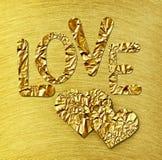 Δύο χρυσές καρδιές και ΑΓΑΠΗ στο χρυσό βουρτσισμένο χάλυβας υπόβαθρο στοκ φωτογραφίες