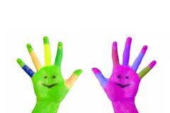 Δύο χρωματισμένα ζωηρόχρωμα χέρια με τα πρόσωπα χαμόγελου Στοκ φωτογραφία με δικαίωμα ελεύθερης χρήσης