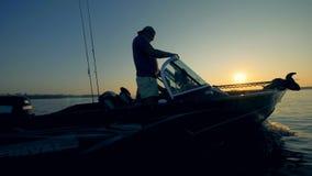 Δύο ψαράδες οδηγούν ένα autoboat για την αλιεία στην ανατολή απόθεμα βίντεο
