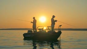 Δύο ψαράδες πιάνουν τα ψάρια στεμένος σε μια βάρκα κατά τη διάρκεια της ανατολής απόθεμα βίντεο