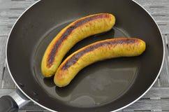 Δύο ψημένα στη σχάρα λουκάνικα σε ένα τηγανίζοντας τηγάνι Στοκ εικόνα με δικαίωμα ελεύθερης χρήσης
