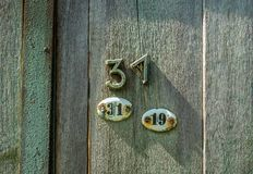 Δύο ωοειδή μεταλλικά πιάτα με τα nubers τριάντα ένα και δεκαεννέα και αριθμός τριάντα ένα που καρφώνονται στην ξύλινη πόρτα στοκ εικόνες