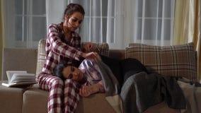 Δύο όμορφα δίδυμα στις πυτζάμες τους στο δωμάτιο το βράδυ Ένα κορίτσι διαβάζει ένα βιβλίο ενώ η αδελφή της κοιμάται απόθεμα βίντεο